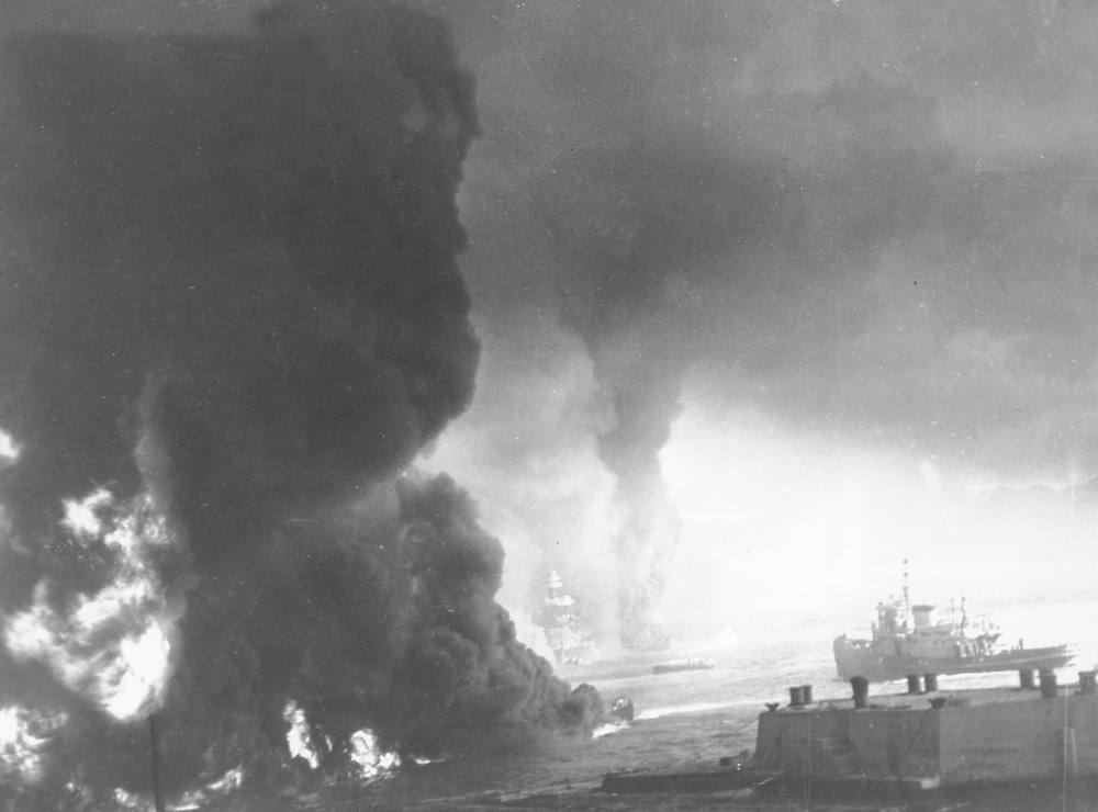 . Heavy black smoke billows as oil fuel burns from shattered tanks on ships that were hit during the Japanese attack on Pearl Harbor, Hawaii on Dec. 7, 1941 during World War II.  Visible through the murk is the U.S. battleship Maryland, center, and the hulk of the capsized USS Oklahoma to the right of it.  (AP Photo/U.S. Navy)