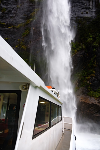 View from boat on Milford Sound, South Island, New Zealand. The front of the boat is taken very close to the waterfall.