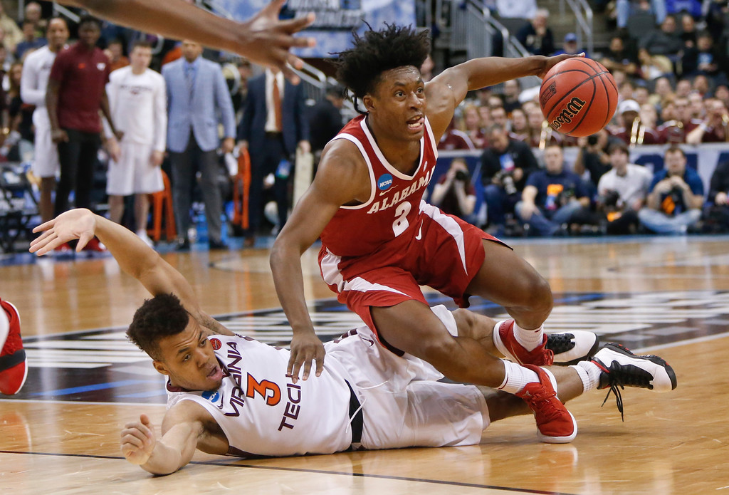 . Alabama\'s Collin Sexton (2) tumbles over Virginia Tech\'s Wabissa Bede (3) during the second half of an NCAA men\'s college basketball tournament first-round game Thursday, March 15, 2018, in Pittsburgh. Alabama won 86-83. (AP Photo/Keith Srakocic)