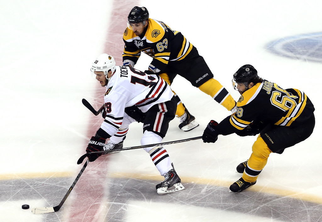 . Jonathan Toews #19 of the Chicago Blackhawks handles the puck against Brad Marchand #63 and Jaromir Jagr #68 of the Boston Bruins during the first period in Game Four of the 2013 NHL Stanley Cup Final at TD Garden on June 19, 2013 in Boston, Massachusetts.  (Photo by Bruce Bennett/Getty Images)