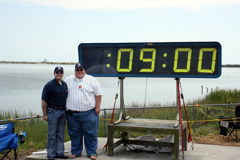 Craig and Chris, sporting STS-125 mission caps, with the countdown clock holding at T minus 9 minutes to liftoff, with Space Shuttle Atlantis on Launch Pad 39-A in the background