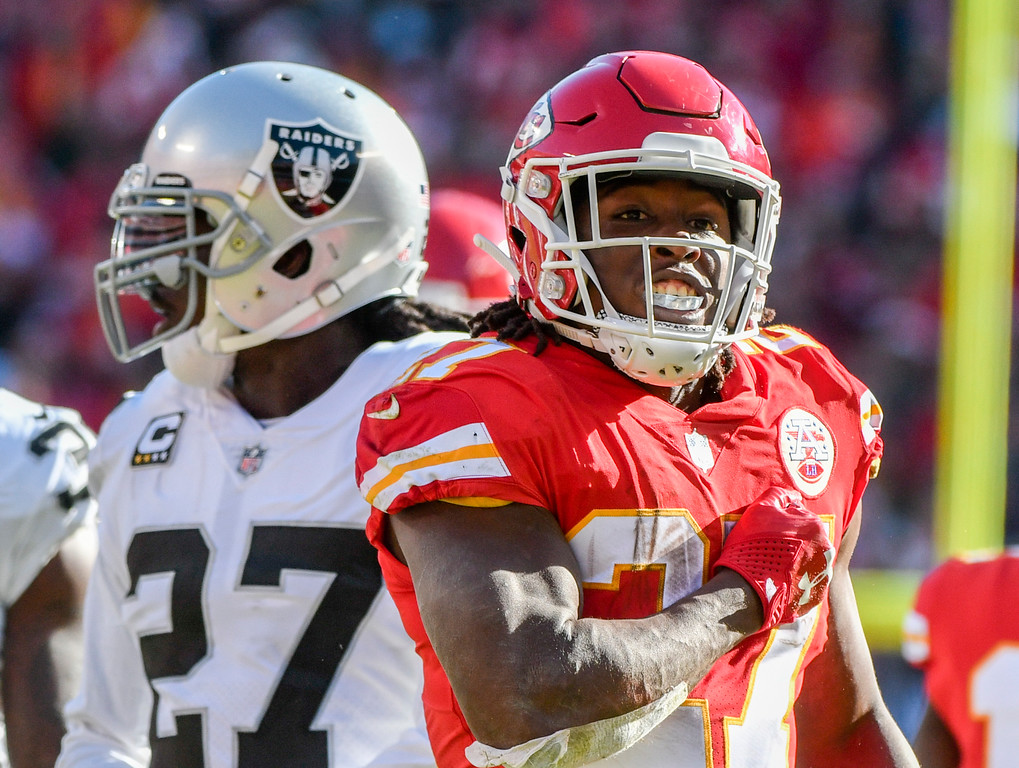 . Kansas City Chiefs running back Kareem Hunt (27) reacts after carrying the ball, in front of Oakland Raiders safety Reggie Nelson (27) during the first half of an NFL football game in Kansas City, Mo., Sunday, Dec. 10, 2017. (AP Photo/Ed Zurga)