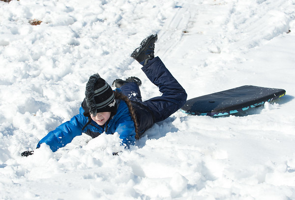 03/04/19 Wesley Bunnell | Staff Xavier Matias, age 9, slides off of his snow board at Walnut Hill Park while sledding with family and friends.