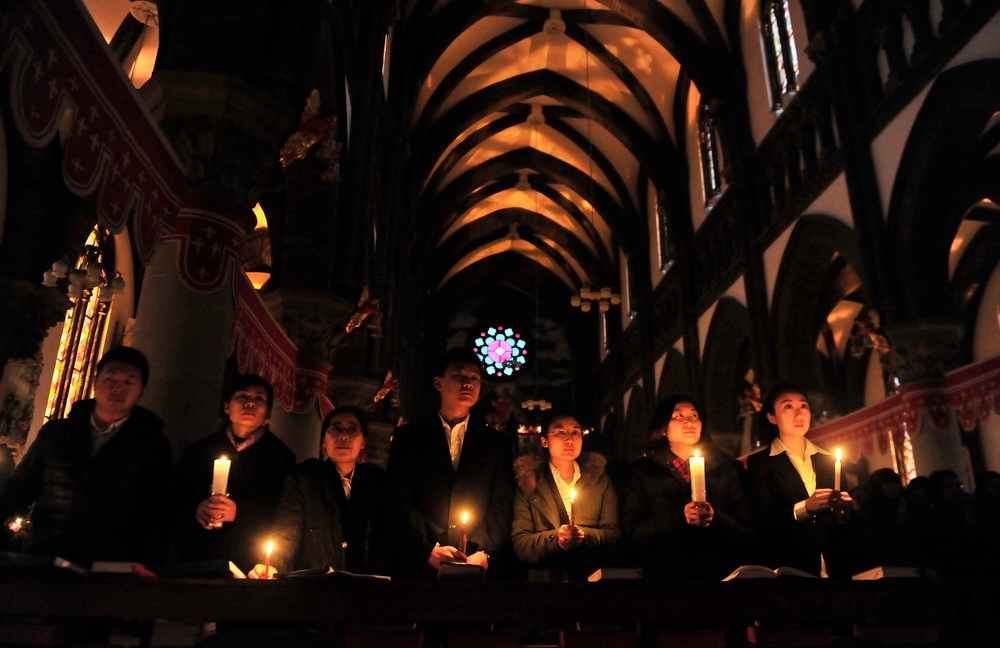 . Worshippers holding candles attend an Easter mass on the eve of Easter, at a Catholic church in Shenyang, Liaoning province, March 30, 2013. Picture taken March 30, 2013. REUTERS/Stringer