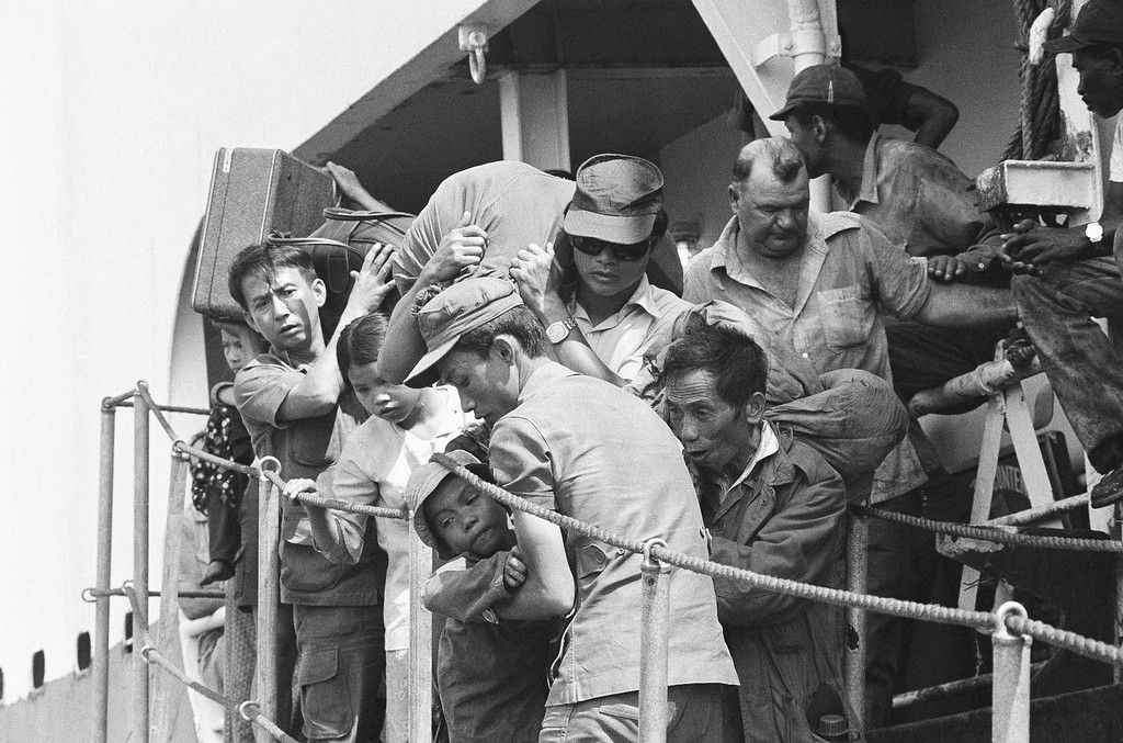 . South Vietnamese refugees disembark at Cam Ranh Bay in Vietnam, Saturday, March 30, 1975 on South Vietnam?s central coast following a voyage from Da Nang, the city which has since fallen to communist forces. Westerner at right is a member of the ship?s crew. (AP Photo/Nick Ut)