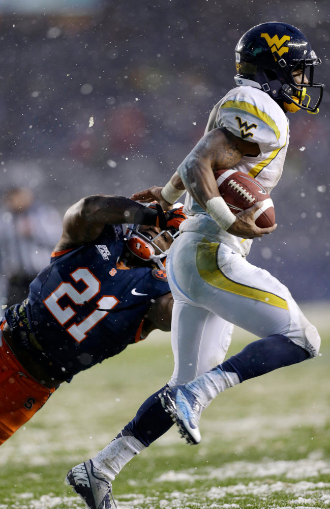 Description of . Syracuse safety Shamarko Thomas (21) tries to tackle West Virginia wide receiver Tavon Austin during the first half of the Pinstripe Bowl NCAA college football game at Yankee Stadium in New York, Saturday, Dec. 29, 2012.  (AP Photo/Kathy Willens)