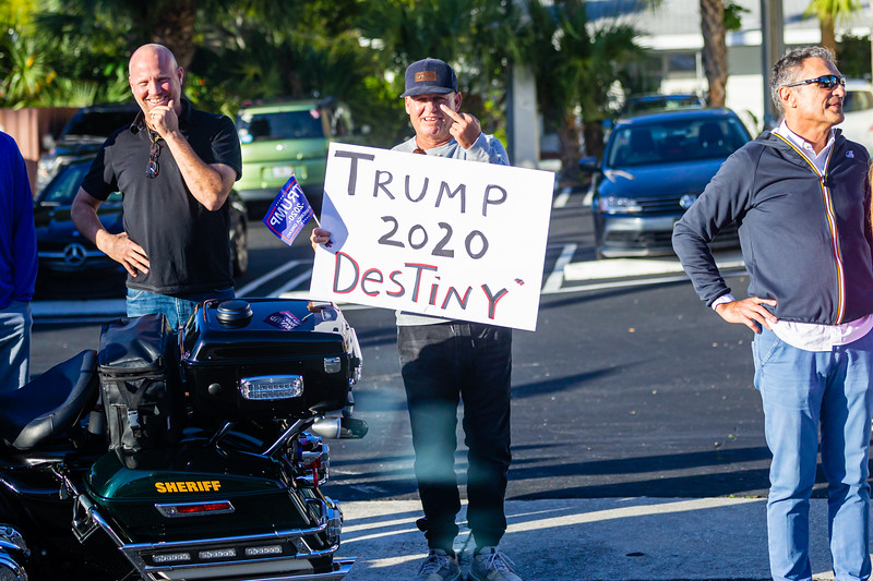 A supporter of President Donald J. Trump greet the media while holding a Trump 2020 Destiny sign  as the Presidential motorcade passes by on Southern Blvd., on Sunday, January 05, 2020. [JOSEPH FORZANO/palmbeachpost.com]