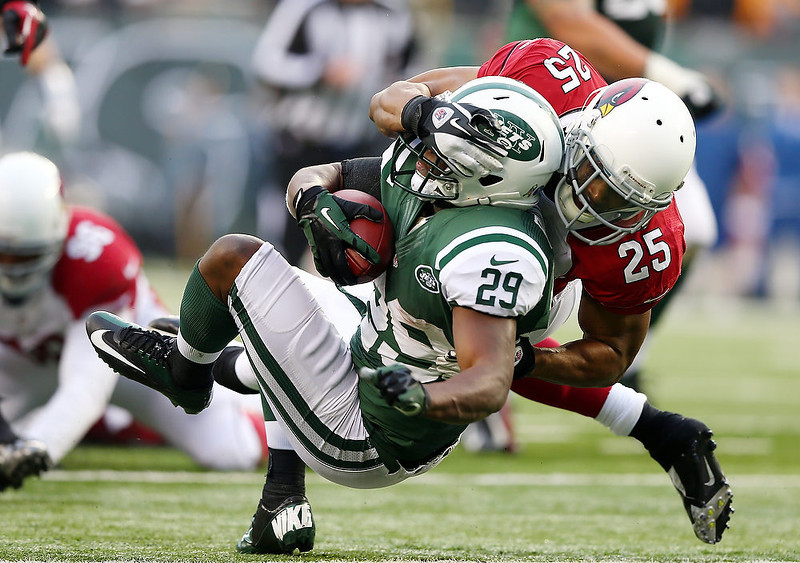 . Bilal Powell #29 of the New York Jets is tackled by Kerry Rhodes #25 of the Arizona Cardinals on December 2, 2012 at MetLife Stadium in East Rutherford, New Jersey. The New York Jets defeated the Arizona Cardinals 7-6.(Photo by Elsa/Getty Images)