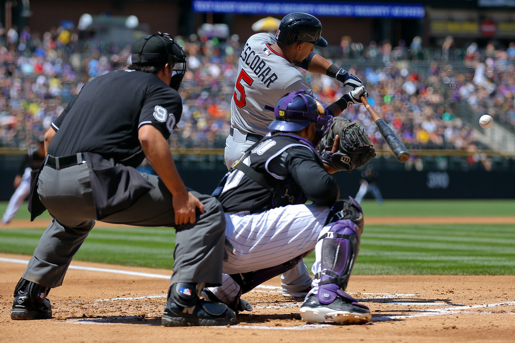 . Eduardo Escobar #5 of the Minnesota Twins hits a two RBI double during the first inning as catcher Wilin Rosario #20 of the Colorado Rockies and home plate umpire Mark Ripperger look on during the first inning. (Photo by Justin Edmonds/Getty Images)