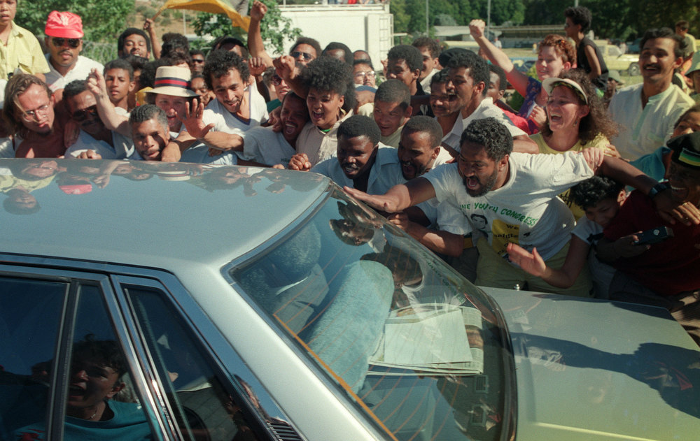 Description of . Anti-apartheid leader and African National Congress (ANC) member Nelson Mandela rides in car through cheering fans as exiting from Victor Verster prison upon his release, 11 February 1990.        (Photo credit should read ALEXANDER JOE/AFP/GettyImages)