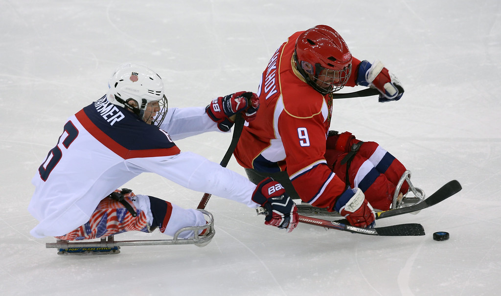 . Declan Farmer (L) of the USA fights for the puck with Konstantin Shikhov (R) of Russia during the Ice Sledge Hockey final  match at Sochi 2014 Paralympic Games, Russia, 15 March 2014.  EPA/SERGEI CHIRIKOV