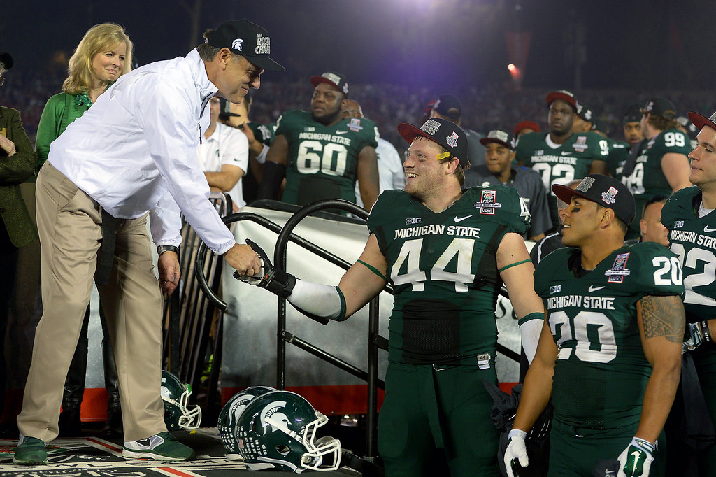 . Michigan State head coach Mark Dantonio shakes hands with his team during the trophy presentation after beating Stanford 24-20 at the Rose Bowl, Wednesday, January 1, 2014. (Photo by Michael Owen Baker/L.A. Daily News)