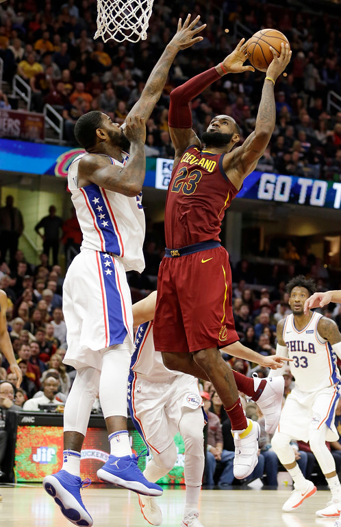 . Cleveland Cavaliers\' LeBron James, right, drives to the basket Philadelphia 76ers\' Amir Johnson during the second half of an NBA basketball game Saturday, Dec. 9, 2017, in Cleveland. The Cavaliers won 105-98. (AP Photo/Tony Dejak)