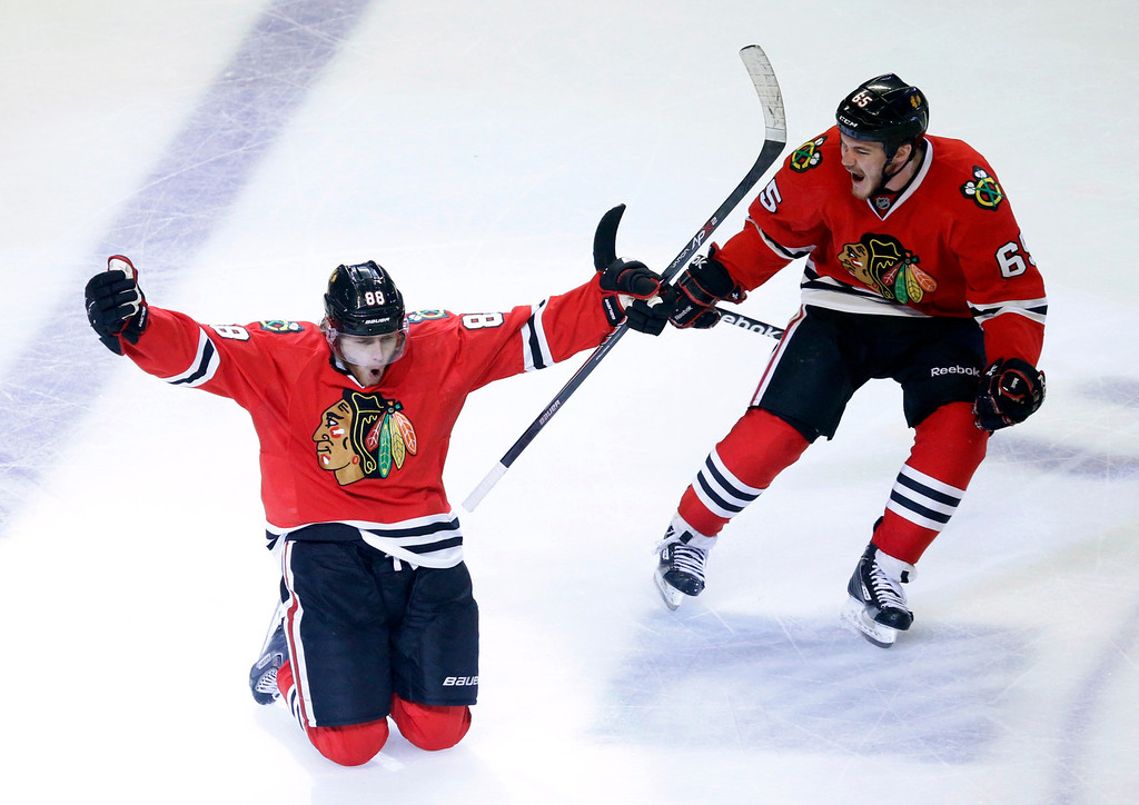 . Chicago Blackhawks right wing Patrick Kane (88) celebrates his goal with center Andrew Shaw (65) during the second overtime period in Game 5 of the NHL hockey Stanley Cup playoffs Western Conference finals against the Los Angeles Kings, Saturday, June 8, 2013, in Chicago. The Blackhawks won 4-3 and advanced to the Stanley Cup finals. (AP Photo/Charles Rex Arbogast)