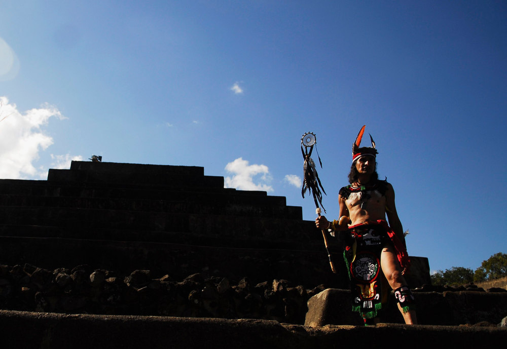 . Piche Ulysses (nahual Mountain) stands in front of a pyramid at the Mayan archeological site of Tazumal in Santa Ana, El Salvador, about  75 km (47 miles) from San Salvador on December 21, 2012. Mystics, hippies and tourists descended on the ruins of Maya cities to mark the close of the 13th bak\'tun - a period of around 400 years - and many hoped it would lead to a better era for humanity. This week, at sunrise on Friday, December 21, an era closes in the Maya Long Count calendar, an event that has been likened by different groups to the end of days, the start of a new, more spiritual age or a good reason to hang out at old Maya temples across Mexico and Central America.  REUTERS/Ulises Rodriguez