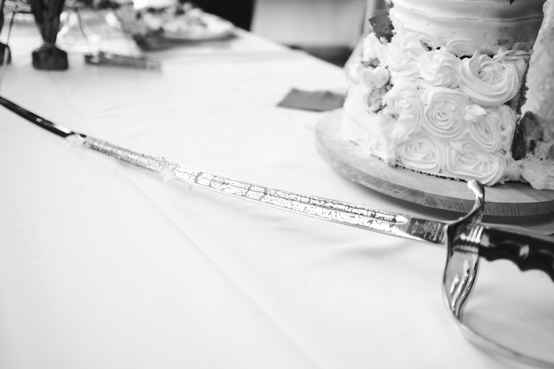 The groom's sword lays on the table, covered in cake and frosting.