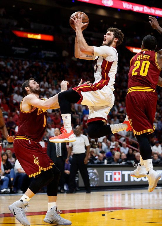 . Miami Heat guard Tyler Johnson goes up for a shot against Cleveland Cavaliers guard Kay Felder (20) and forward Kevin Love (0) during the second half of an NBA basketball game, Monday, April 10, 2017, in Miami. Johnson scored 24 points as the Heat defeated the Cavaliers 124-121 in overtime. (AP Photo/Wilfredo Lee)