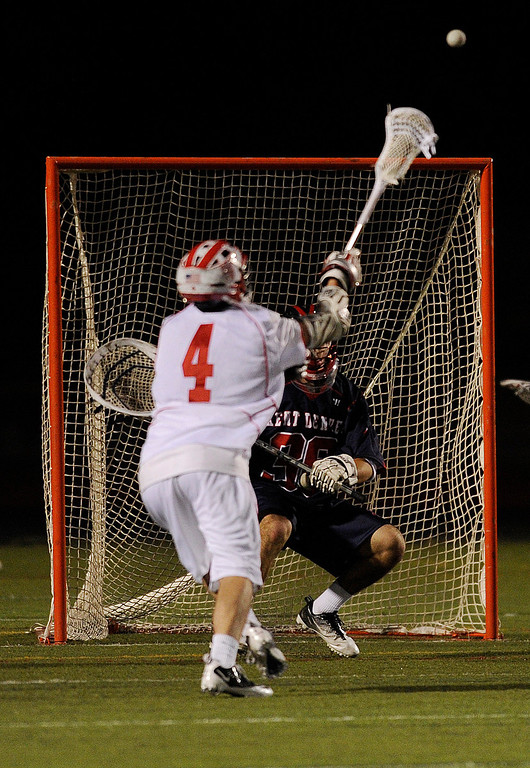 . AURORA, CO. - APRIL 24:  Regis attack Chet Dunstan (4) grabbed a rebound in front of the net and slammed it past Kent Denver goalie Marcus Stears (36) in the second half. The Regis Jesuit High School boy\'s lacrosse team defeated Kent Denver 10-8 Wednesday night, April 24, 2013. Photo By Karl Gehring/The Denver Post