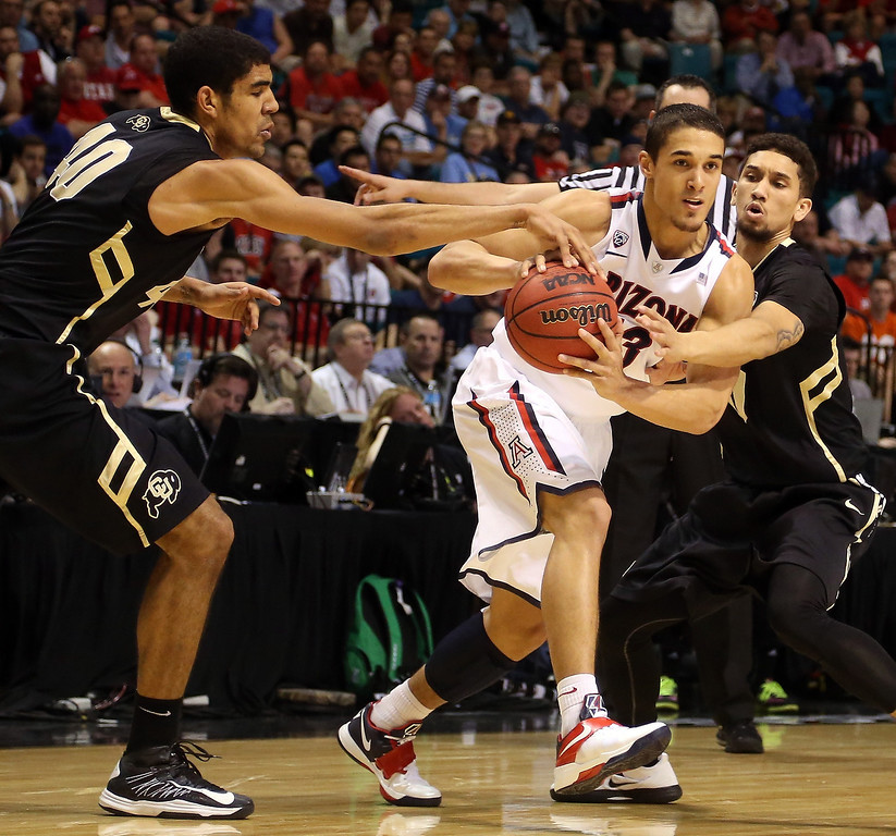 . Nick Johnson #13 of the Arizona Wildcats is double-teammed by Josh Scott #40 and Askia Booker #0 of the Colorado Buffaloes in the second half during the quarterfinals of the Pac-12 tournament at the MGM Grand Garden Arena on March 14, 2013 in Las Vegas, Nevada.  (Photo by Jeff Gross/Getty Images)