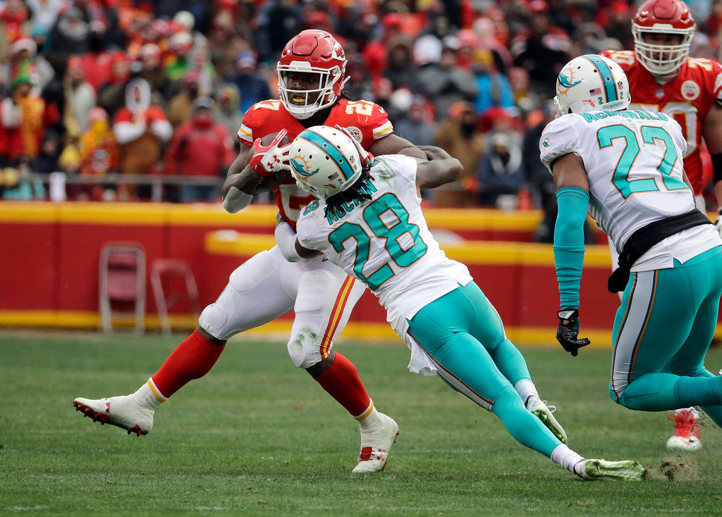 . Kansas City Chiefs running back Kareem Hunt (27) is tackled by Miami Dolphins cornerback Bobby McCain (28) during the first half of an NFL football game in Kansas City, Mo., Sunday, Dec. 24, 2017. (AP Photo/Charlie Riedel)