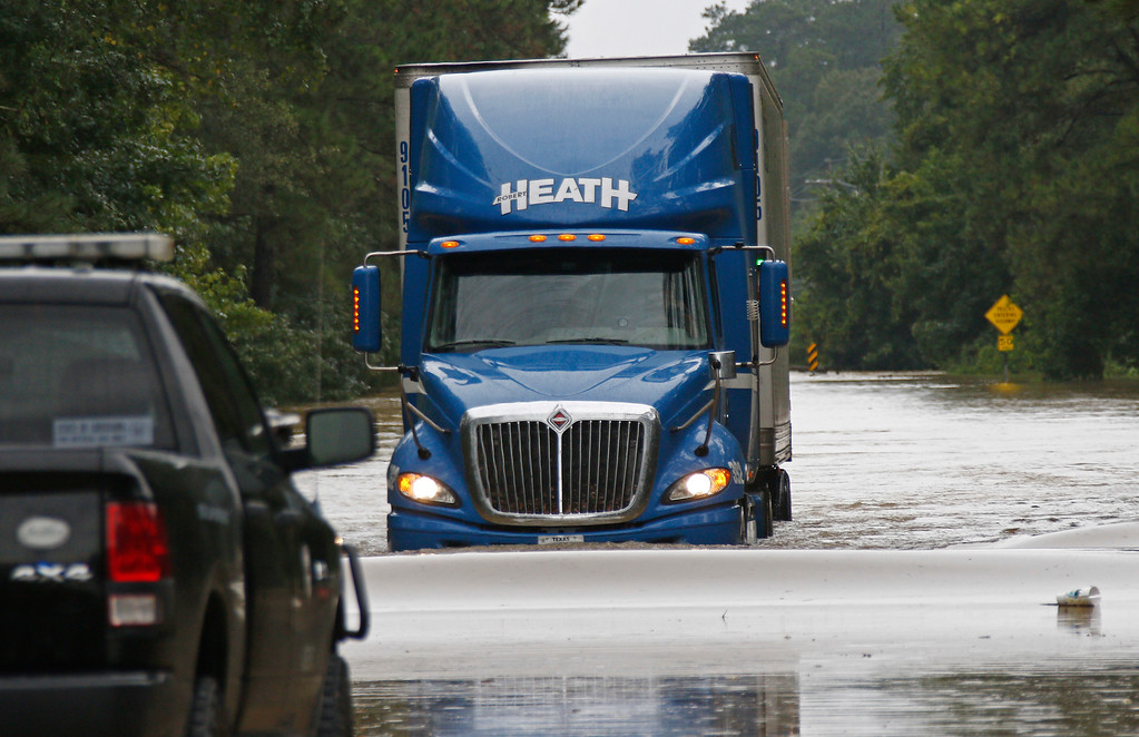 ". Mike McBride, of Monroe, drives his tractor trailer rig through the Natalbany River flood waters in Baptist, La., Saturday, Aug. 13, 2016. McBride was trying to get to drive to Texas when he was rerouted several times and took a chance at driving across the flooded street. A slow-moving storm that has dumped almost a foot of rain in Louisiana parishes south and west and Mississippi counties north of the Mississippi-Louisiana state line, are in for more rain. National Guard soldiers and other officials in boats and helicopters plucked more than 1,000 people from their homes and cars as ""unprecedented, historic\"" flooding swamped Louisiana, the governor said Saturday. (AP Photo/Rogelio V. Solis)"