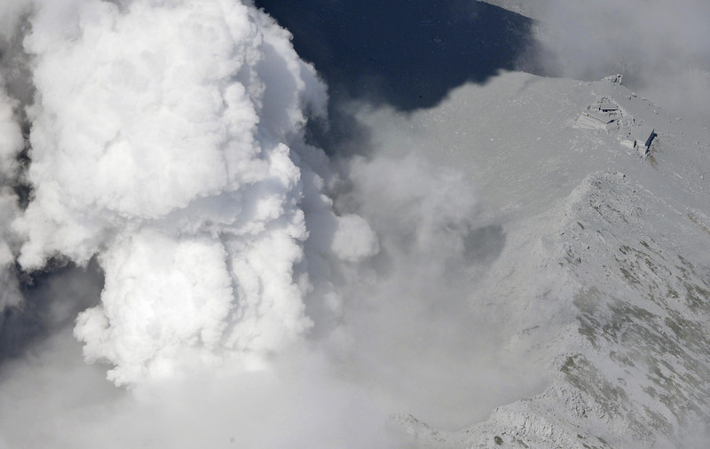 . Mountain lodge buildings totally covered by ash stand on the edge of the crater as white plumes are spewed out from Mt. Ontake in central Japan Saturday, Sept. 27, 2014. With a sound likened to thunder, the 3,067-meter (10,062-foot) volcanic mountain spewed large white plumes high into the sky, sending people fleeing and covering surrounding areas in ash. (AP Photo/Kyodo News)