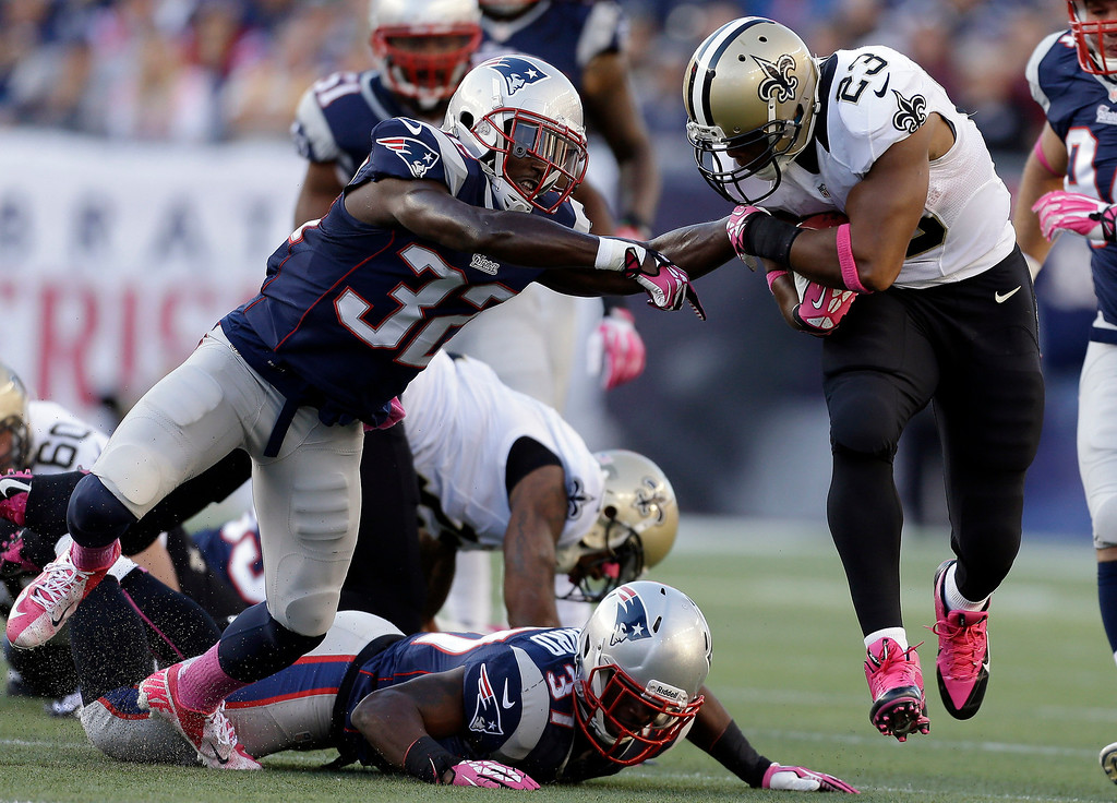 . New England Patriots free safety Devin McCourty (32) tackles New Orleans Saints running back Pierre Thomas (23) in the first half of an NFL football game Sunday, Oct.13, 2013, in Foxborough, Mass. (AP Photo/Steven Senne)