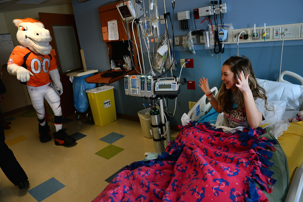 . Madeline Conley, 15, reacts with delight as she Miles, the Broncos Mascot, makes a surprise visit to her in her room in the Pediatric Intensive Care Unit at the  Rocky Mountain Hospital for Children in Denver, Co on January 14, 2014. Conley was diagnosed with leukemia just 3 days ago.   (Photo By Helen H. Richardson/ The Denver Post)
