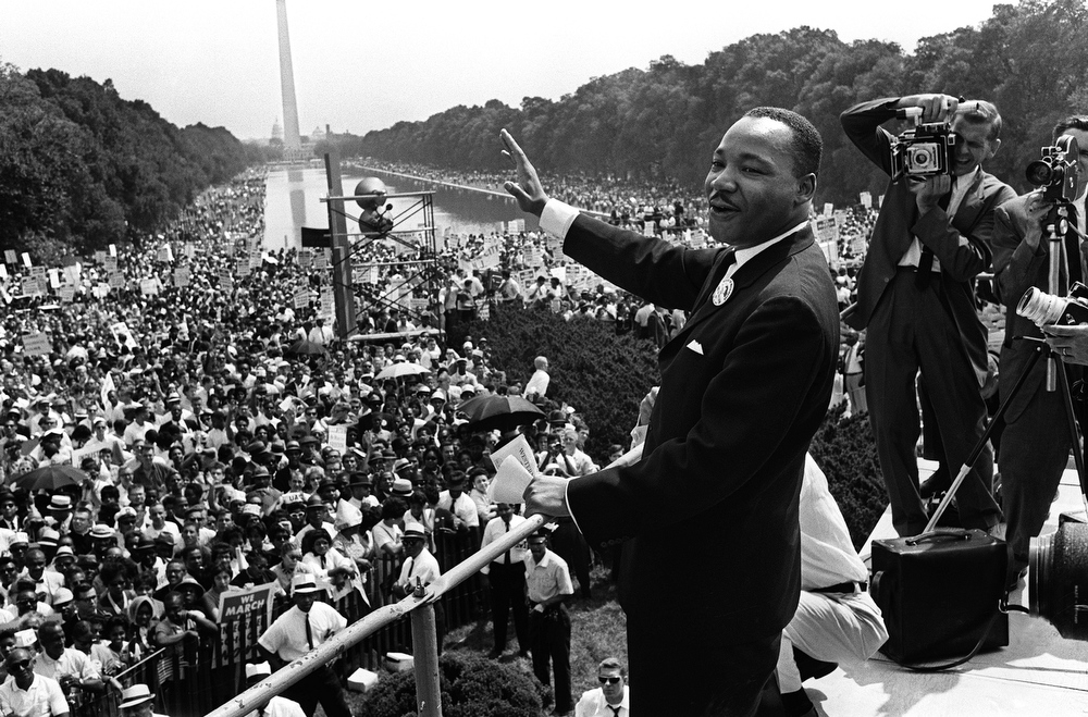 Description of . Civil rights leader Martin Luther King (C) waves to supporters 28 August 1963 on the Mall in Washington, DC, during the