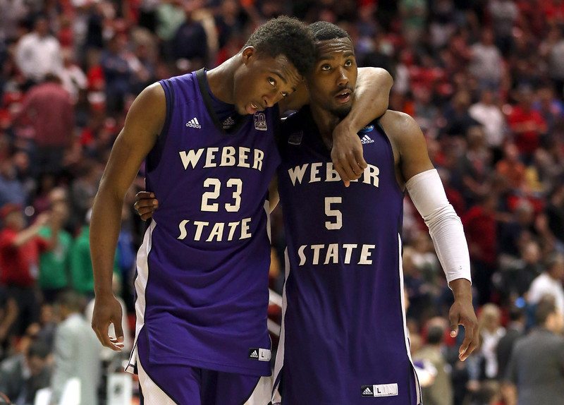. Richaud Gittens #23 and Jordan Richardson #5 of the Weber State Wildcats walk off the court after losing to the Arizona Wildcats during the second round of the 2014 NCAA Men\'s Basketball Tournament at Viejas Arena on March 21, 2014 in San Diego, California.  (Photo by Jeff Gross/Getty Images)