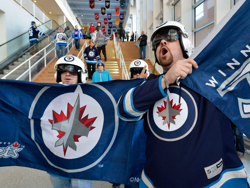Description of . Winnipeg Jets fans Tyler MacFarland (L) and Norman Lavallee cheer as they arrive at the MTS Centre for the first game of the NHL hockey season against Ottawa Senators in Winnipeg January 19, 2013. The NHL begins a condensed 48-game season today after a 113-day labour dispute. REUTERS/Fred Greenslade