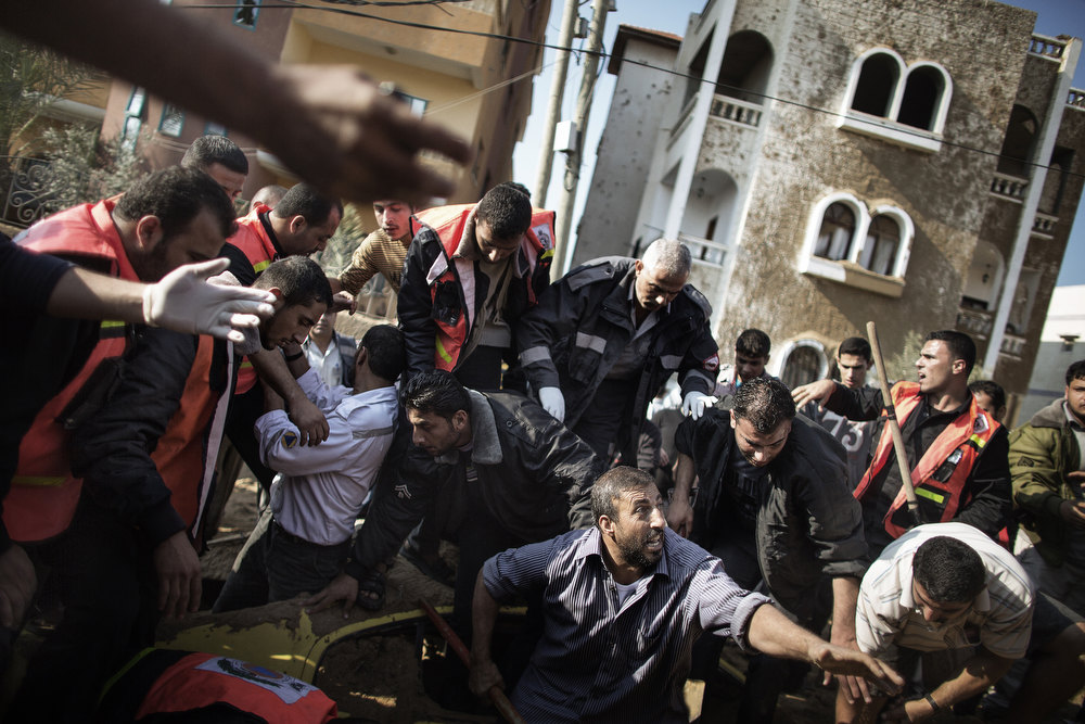 Description of . A Palestinian man calls for help as he and others try to save a man  trapped under his car just after an Israeli air raid on the area of Twaam in the northern Gaza town of Beit Lahia on November 15, 2012. Israeli air strikes have killed more than ten Gazans, including top Hamas commander Ahmed Jaabari, as three Israelis die when a rocket strikes a house, in the latest flareup of tit-for-tat fighting. MARCO LONGARI/AFP/Getty Images