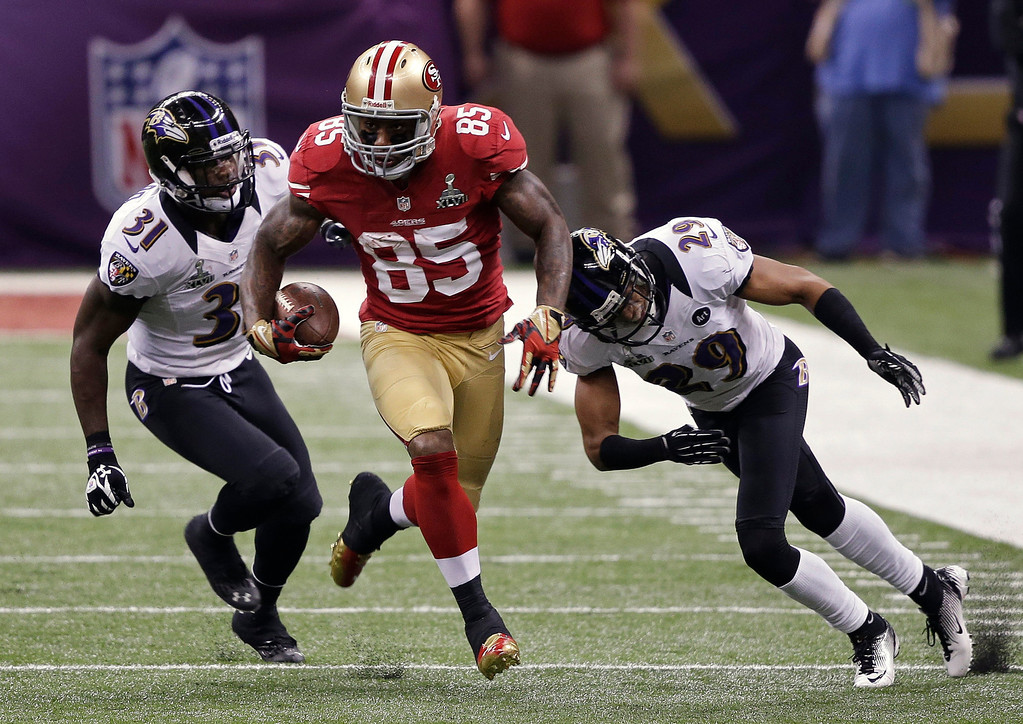 . San Francisco 49ers tight end Vernon Davis (85) runs with the ball as Baltimore Ravens safety Bernard Pollard (31) and cornerback Cary Williams (29) give chase during the first half of the NFL Super Bowl XLVII football game, Sunday, Feb. 3, 2013, in New Orleans. (AP Photo/Bill Haber)