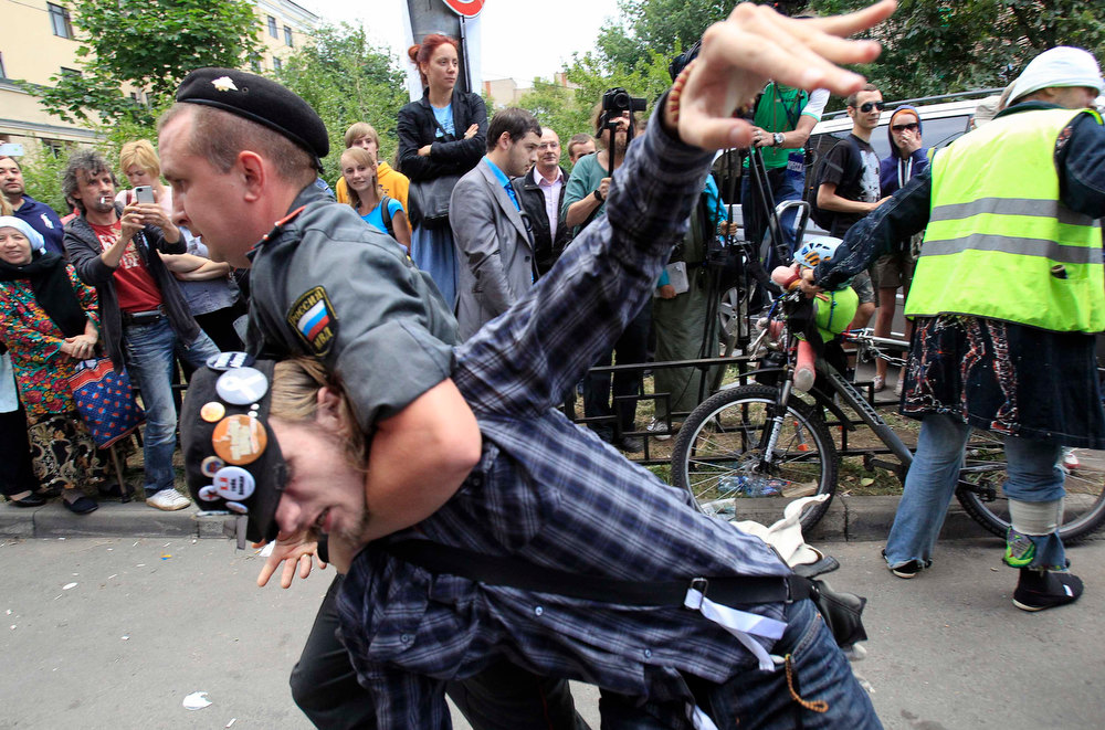 ". Police detain a supporter of the female punk band ""Pussy Riot\"" members for violation of law and order outside a court building in Moscow, August 17, 2012. Three women from Russian punk band Pussy Riot were sentenced to two years in jail on Friday for their protest against President Vladimir Putin in a church, an outcome supporters described as the Kremlin leader\'s \""personal revenge\"". \""Pussy Riots\"" ranked as Google\'s tenth most searched trending event of 2012. REUTERS/Sergei Karpukhin"