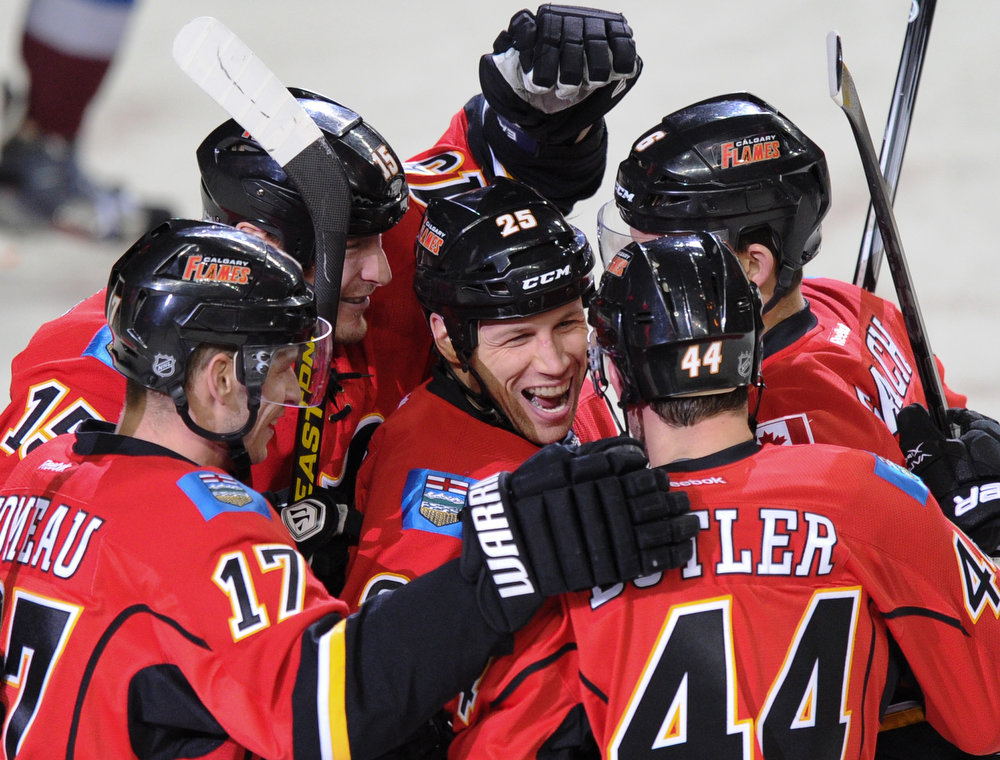 . Calgary Flames\' Steve Begin (25) is mobbed by teammates after scoring against the Colorado Avalanche during the first period of their NHL hockey game in Calgary, Alberta, March 27, 2013. REUTERS/Mike Sturk