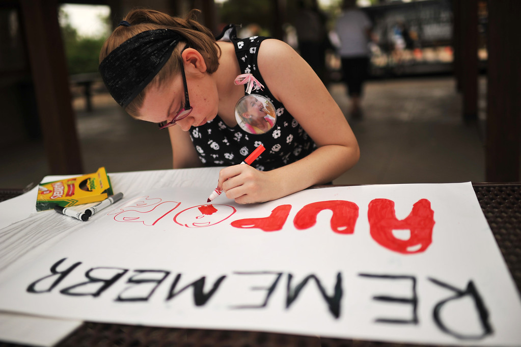 . AURORA, CO. - July 19: Stephanie Richards, 12, of Golden makes a sign for the memorial at Smokey Hill Shelter in Cherry Creek State Park. Aurora, Colorado. July 19, 2013. Two groups met at the park to mark the first anniversary of the Aurora movie theater massacre � one to remember those killed by guns, and the other rally to support the Second Amendment. (Photo By Hyoung Chang/The Denver Post)