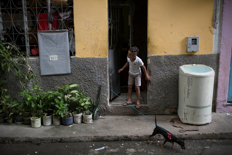 """. A young resident looks out from his home as military police officers patrol during an operation in the Mare slum complex, ahead of its \""""pacification,\"""" in Rio de Janeiro, Brazil, Tuesday, March 25, 2014. (AP Photo/Felipe Dana)"""