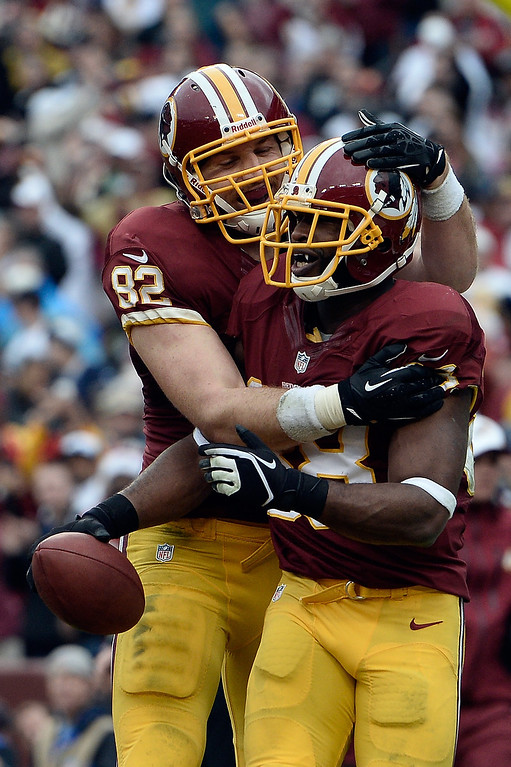 . Pierre Garcon #88 celebrates with Logan Paulsen #82 of the Washington Redskins after scoring a touchdown in the third quarter during an NFL game against the Dallas Cowboys at FedExField on December 22, 2013 in Landover, Maryland.  (Photo by Patrick McDermott/Getty Images)