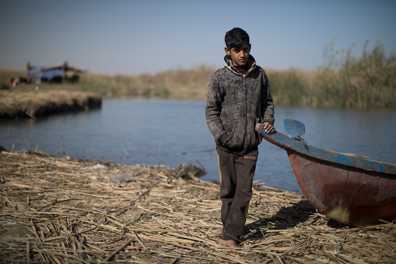 A boy on a small island constructed from a mass of reeds and mud. The Qurna Marshes, one of three wetland areas that form the Mesopotamian Marshes, cover an area of around 3000 square kilometres.