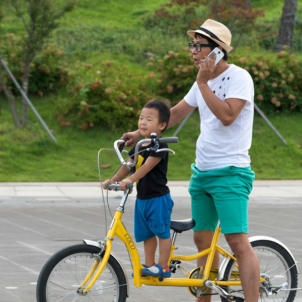 Man talking on mobile phone with his son on bicycle, Seoul, South Korea