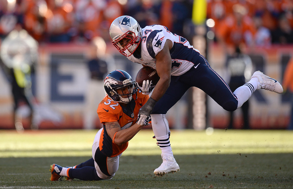 . New England Patriots running back Shane Vereen (34) is tackled by Denver Broncos cornerback Tony Carter (32) in the third quarter. The Denver Broncos take on the New England Patriots in the AFC Championship game at Sports Authority Field at Mile High in Denver on January 19, 2014. (Photo by Hyoung Chang/The Denver Post)