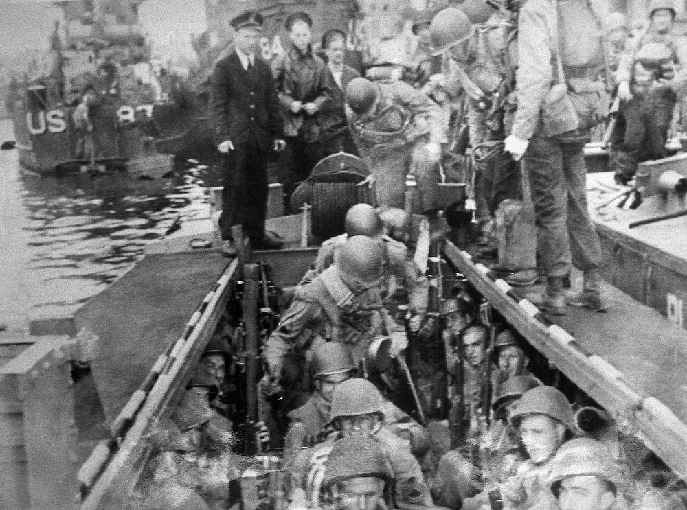 Description of . Fully equipped, and each carring large amounts of ammunition, American troops climb aboard a landing craft somewhere in England for the cross-channel invasion of France June 6, 1944. Other landing crafts are seen in background. (AP Photo)