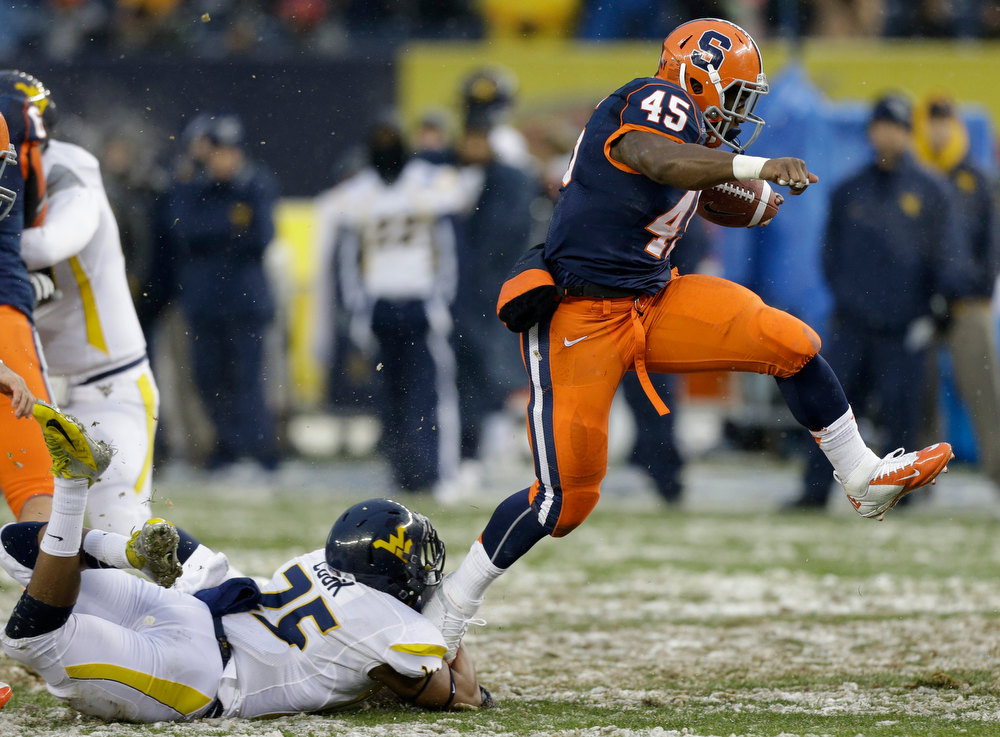 Description of . Syracuse running back Jerome Smith (45) escapes the grasp of West Virginia safety Darwin Cook (25) during the first half of the Pinstripe Bowl NCAA college football game at Yankee Stadium in New York, Saturday, Dec. 29, 2012. (AP Photo/Kathy Willens)