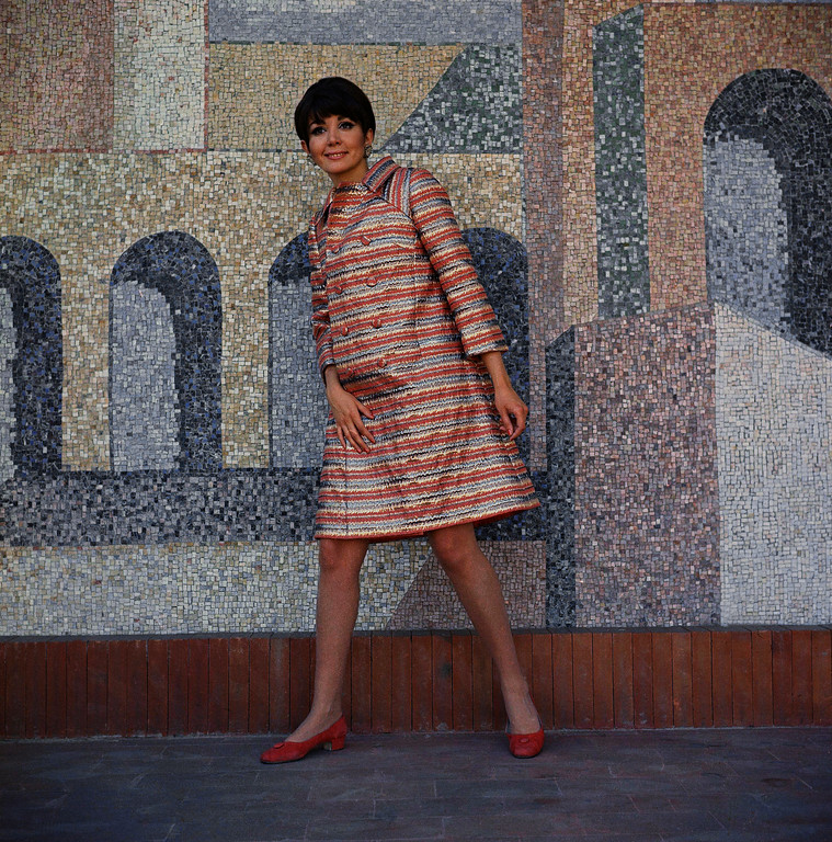 . A red-orange wooden coat, with laminated silver and golden horizontal stripes, by Renato Balestra of Rome, modeled by Gilda Giuffrida. Can be worn over a dress of red-orange creped wool, with matching shoes fashion Italian coat in 1967. (AP Photo/Mario Torrisi)