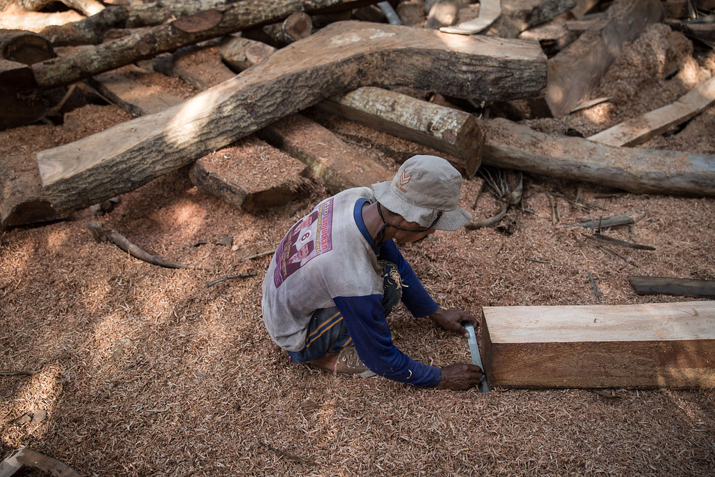 . A Buginese man measures a wooden block at Tanjung Bira Beach on May 2, 2014 in Bulukumba, South Sulawesi, Indonesia.  (Photo by Agung Parameswara/Getty Images)