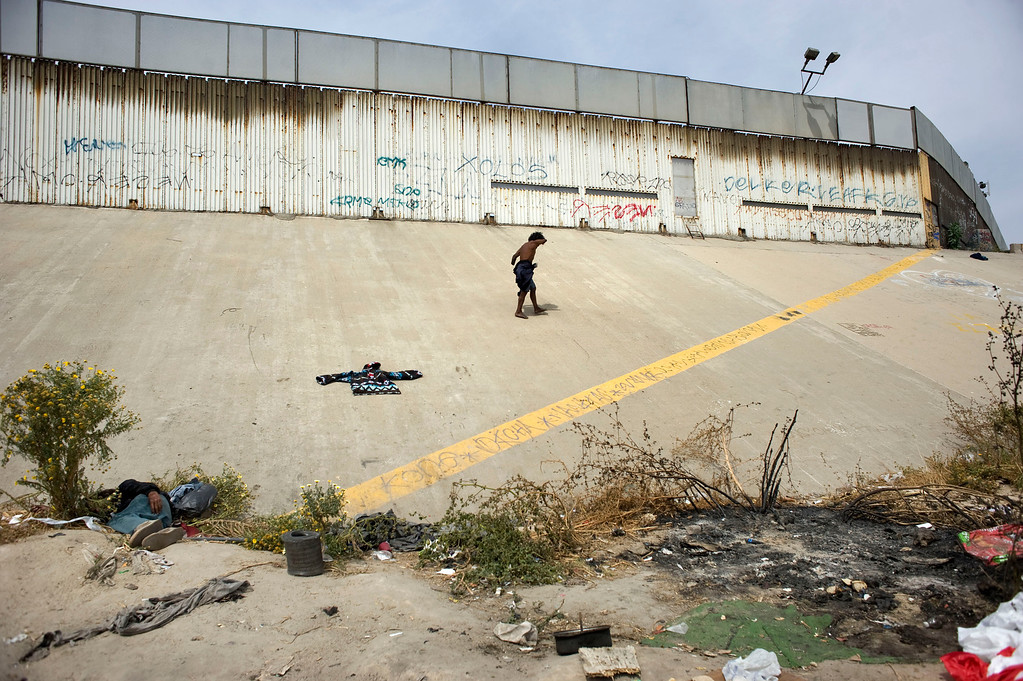 . A homeless man with truncated arms walks next to the US-Mexico border wall on the US side of the international boundry (yellow line), in Tijuana, Mexico, 03 May 2013. Heightened US border security and record numbers of deportations from the US have created a growing population of people who live homeless in Mexican cities that border with the United States. Many had lived for years undocumented in the US and have little or no family and other support in Mexico, and are subject to fall into depression, substance abuse and crime. Tijuana, Mexico, borders on the US city of San Diego, California.  EPA/DAVID MAUNG
