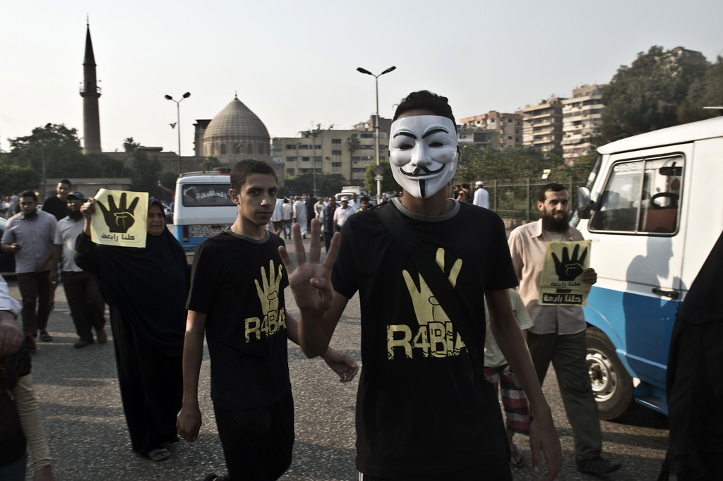 """. Supporters of Egyptian ousted president Mohamed Morsi and of the Muslim brotherhood movement, one wearing a mask of the anonymous movement, wear shirts with the Rabaa sign during a rally outside the al-Quba presidential palace in Cairo on October 11, 2013. An Islamist alliance urged its supporters to stay away from Cairo\'s Tahrir Square during protests to avoid more bloodshed after a week in which nearly 80 Egyptians were killed. The \""""Rabaa\"""", which means four in Arabic, refers to those killed in the crackdown on the Rabaa al-Adawiya protest camp in Cairo earlier in the year.  KHALED DESOUKI/AFP/Getty Images"""