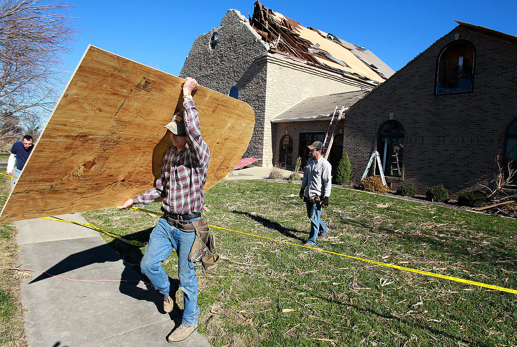 . Matt Brandmeyer of Bartelso carries plywood used to repair the damaged St. John\'s Lutheran Church Monday, Nov. 18, 2013,  in New Minden, Ill. (AP Photo/ Belleville News-Democrat,Steve Nagy)