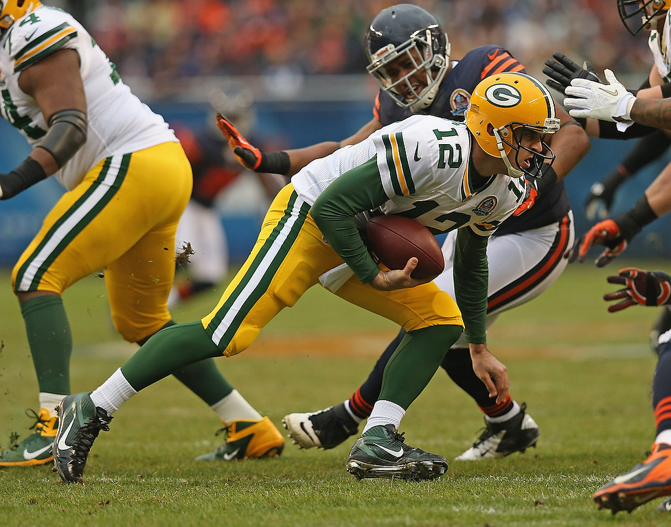 . Aaron Rodgers #12 of the Green Bay Packers moves to avoid rushing members of the Chicago Bears at Soldier Field on December 16, 2012 in Chicago, Illinois. The Packers defeated the Bears 21-13. (Photo by Jonathan Daniel/Getty Images)