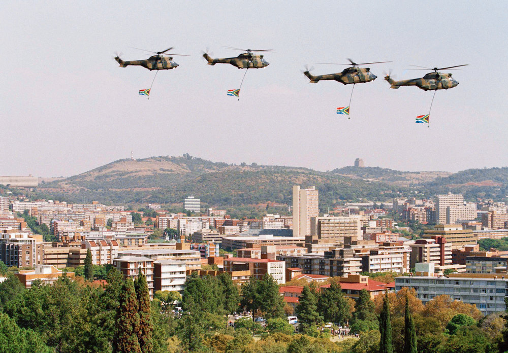 Description of . South African Defense Force helicopters carrying the new South African flag fly over Pretoria during the inauguration ceremony for the country's first black president, Nelson Mandela in Pretoria, South Africa, May 10, 1994. The inauguration finished with a thunderous cannon salute, warplanes trailing smoke in the national colors of red, white, blue, black, green and gold, and these helicopters carrying the redesigned flag. (AP Photo)